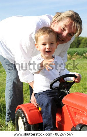 Mother and 2 years young son playing with red tractor