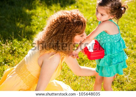 mother and young child in the park enjoying a sunny day - stock photo