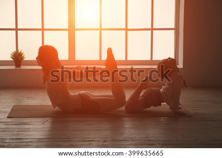 Mother and young daughter doing yoga together. Silhouette fitness woman. Women silhouettes in the window sunset background. Space for text. - stock photo
