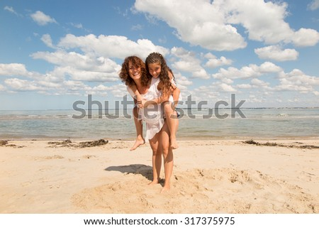 Mother and young  daughter playing on the beach