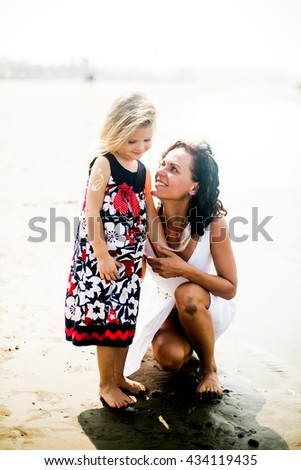 mother and young daughter portrait of summer on the sea - stock photo