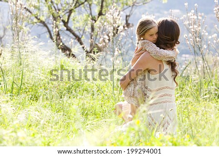 Mother and young daughter relaxing together in a beautiful spring field of green grass and flowers, hugging and enjoying a sunny holiday outdoors. Family love and holiday activities lifestyle. - stock photo