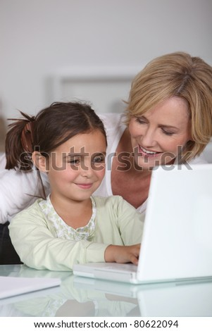 Mother and young daughter using a white laptop computer together