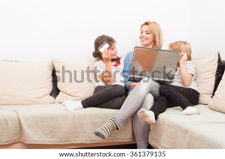 Mother and young daughters shopping online concept using laptop and credit card - stock photo