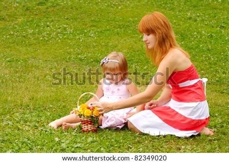 Mother and young girl outdoors embracing and smiling
