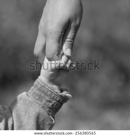 Mother and young son holding hands - stock photo