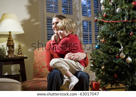 Mother and young son sitting by Christmas tree