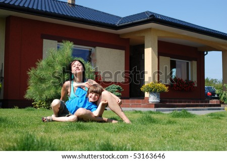 Mother ans son having fun in front of theirs house - stock photo