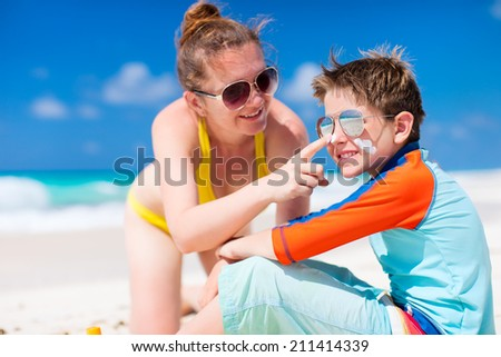 Mother applying sun protection cream to her son at tropical beach during summer vacation - stock photo