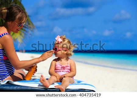 mother applying sunblock cream on daughter shoulder - stock photo