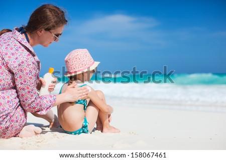 Mother applying sunblock cream on her daughters shoulder - stock photo