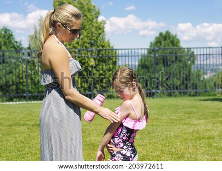 Mother Applying Sunscreen - stock photo