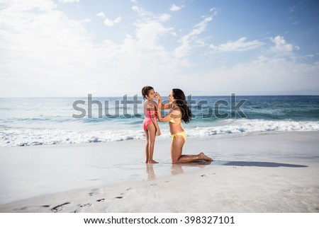 Mother applying sunscreen lotion to her daughter on beach - stock photo