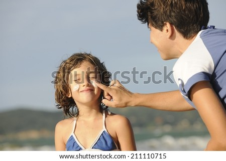 Mother applying sunscreen to daughter at beach. - stock photo