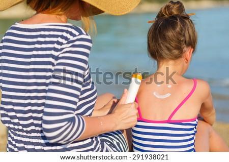 Mother applying suntan cream to her daughter - stock photo