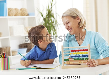 Mother assisting her son to count using an abacus - stock photo