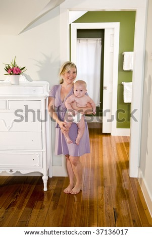Mother at home carrying seven month old baby - stock photo