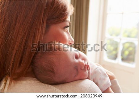 Mother At Home With Sleeping Newborn Baby Daughter - stock photo