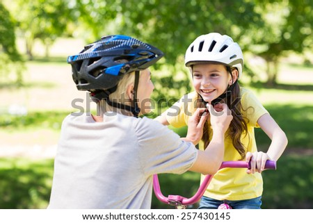 Mother attaching her daughters cycling helmet on a sunny day - stock photo