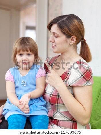Mother berates her baby in home interior - stock photo
