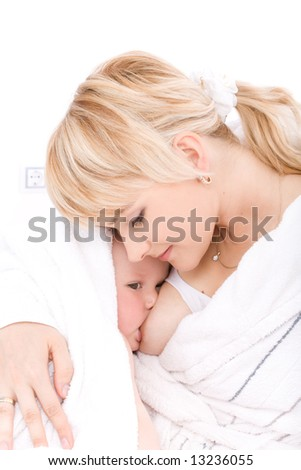 Mother breast feeding her baby girl in white room at home - stock photo