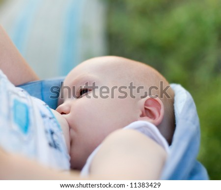 Mother breast feeding her infant in sling (strap of cloth used to carry baby under 2 years) - stock photo