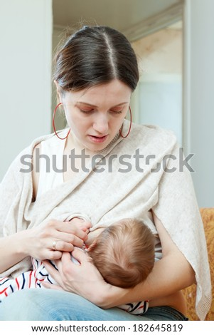 Mother breast feeding her three-month baby at home interior - stock photo