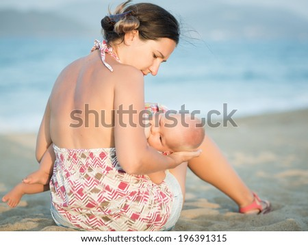 Mother breastfeeding baby on the beach - stock photo