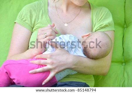Mother breastfeeding her baby girl - stock photo