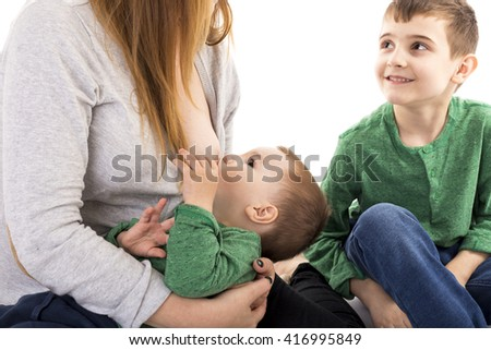 Mother breastfeeding her baby next to her other son over white - stock photo