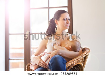 Mother breastfeeding her little baby girl in her arms. - stock photo