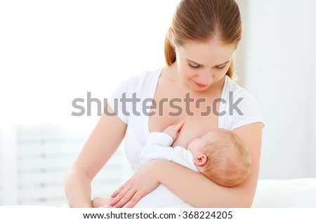 mother breastfeeding her newborn baby in a white bed - stock photo