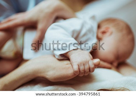 mother breastfeeds her infant , the baby holds hand of mother's hand - stock photo
