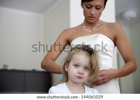 Mother bride brush her daughter's hair - stock photo