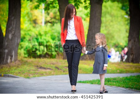 Mother brings her daughter to school. Adorable little girl feeling very excited about going back to school - stock photo