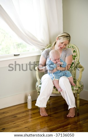 Mother burping baby after bottle-feeding
