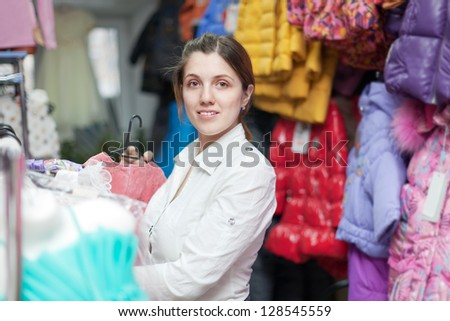 mother buys clothes for little child in children's clothing store - stock photo