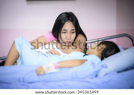 Mother care and worry about her sick daughter; Asian kid sick by broken arm and sleep on hospital bed - stock photo