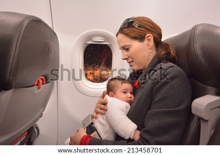 Mother carry her newborn baby during flight.Concept photo of air travel with baby. - stock photo