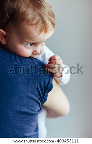 Mother carrying a cute baby girl on her shoulder - stock photo