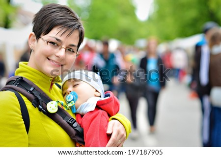 mother carrying baby boy in the city - stock photo