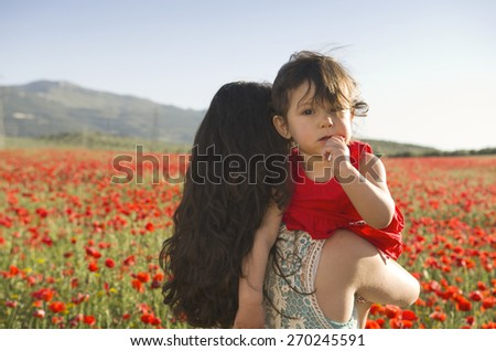 Mother carrying baby daughter at outdoors in spring image at poppies field - stock photo