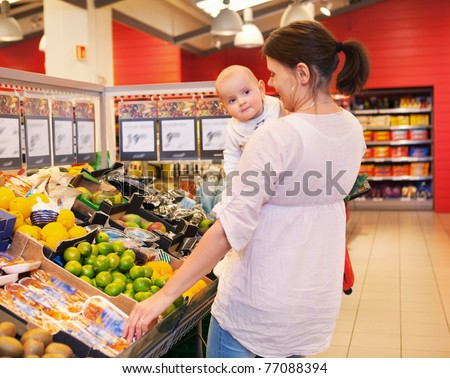 Mother carrying child while shopping in supermarket - stock photo