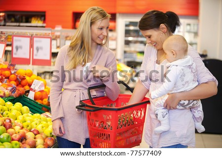 Mother carrying child with friend while shopping in supermarket - stock photo