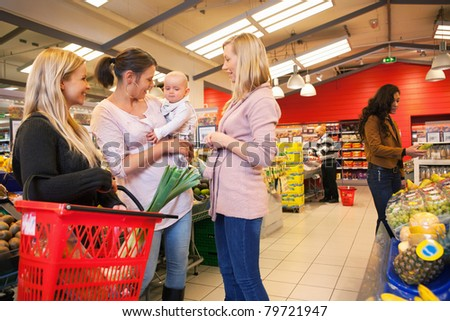 Mother carrying child with friends shopping in supermarket - stock photo