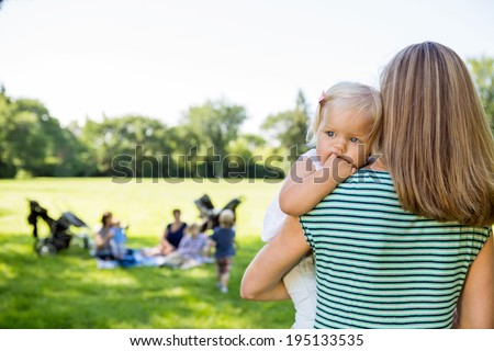 Mother carrying daughter looking away with friends and children in background at park - stock photo