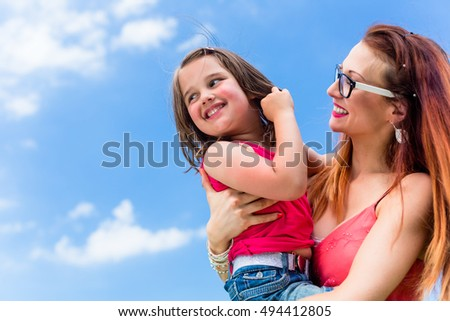 Mother carrying daughter on her arm under a clear blue summer sky