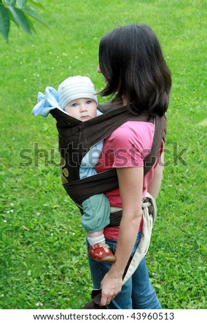 Mother carrying her baby in baby carrier - stock photo