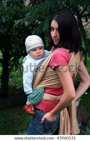 Mother carrying her baby in sling - stock photo