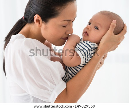 Mother carrying her baby with love - stock photo
